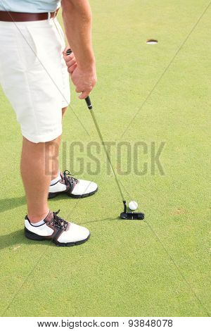 Low section of man playing golf at course