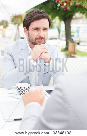 Thoughtful businessman sitting with colleague at sidewalk cafe