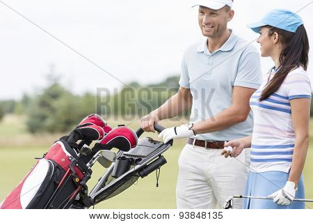 Happy friends with bag talking at golf course