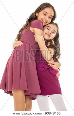 Dark-haired girl sisters in fashionable dresses hugging, close-u