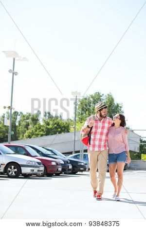 Affectionate couple walking on city street against clear sky