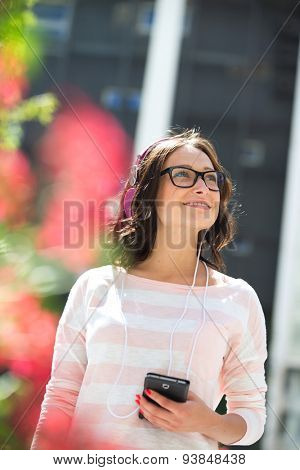 Smiling young woman looking away while listening music outdoors