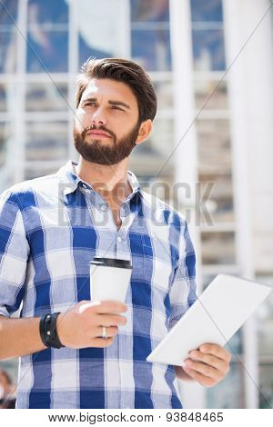 Thoughtful man looking away while holding disposable cup and tablet PC in city