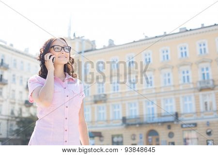 Smiling young woman answering smart phone against building on sunny day