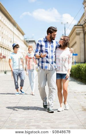 Couple walking on street with friends in background