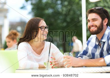 Cheerful couple having mojito at sidewalk cafe