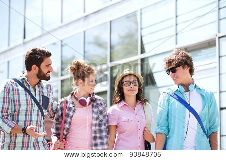 Male and female friends talking outside building