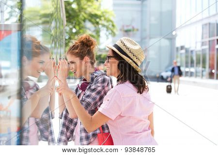 Happy female friends window shopping in city