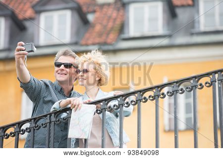 Happy middle-aged couple taking selfie against building