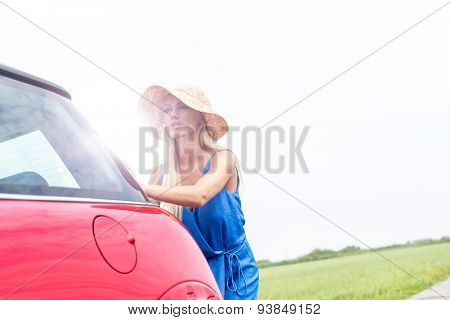 Woman pushing broken down car against clear sky