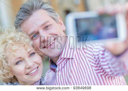 Close-up of happy middle-aged couple taking selfie through smart phone