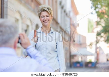 Middle-aged man taking picture of woman in city