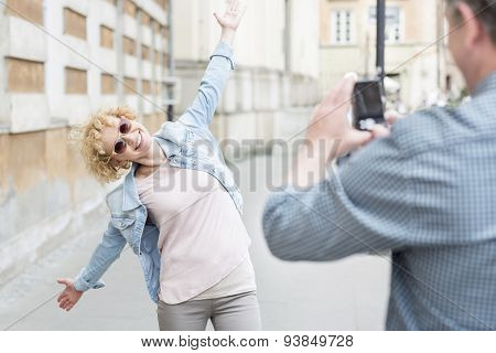 Man photographing playful woman standing with arms outstretched on city street