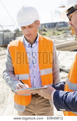 Engineers writing on clipboard at construction site