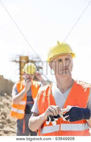 Thoughtful worker standing at construction site with colleague in background