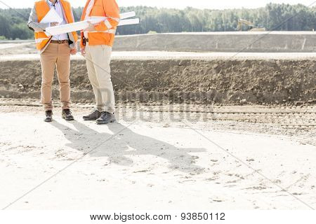 Low section of engineers with blueprints standing at construction site