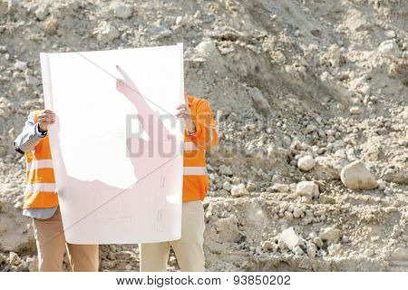 Engineers examining blueprint at construction site