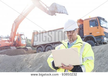 Supervisor using laptop at construction site on sunny day