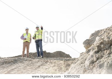 Supervisor discussing with colleague at construction site against clear sky