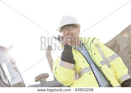 Smiling supervisor using walkie-talkie at construction site against clear sky