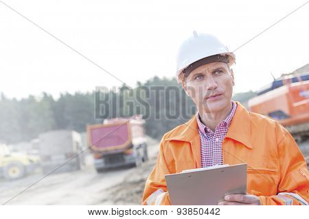 Engineer looking away while holding clipboard against clear sky