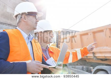 Supervisor showing something to colleague holding laptop at construction site