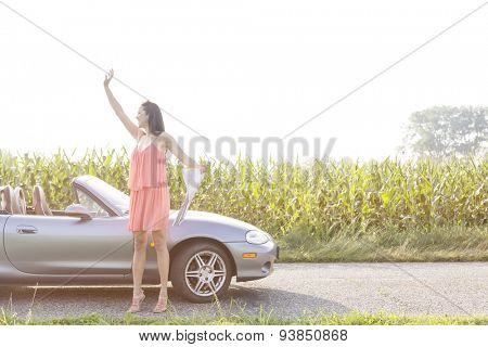 Full length of woman gesturing while holding map by convertible against clear sky