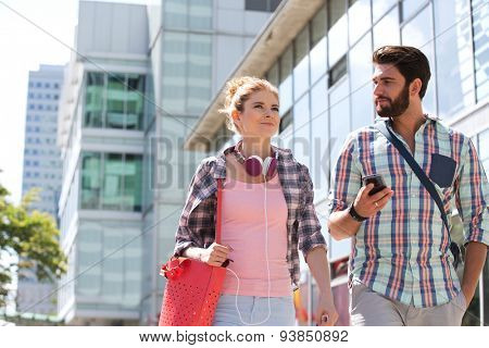 Male and female friends walking outside office building on sunny day