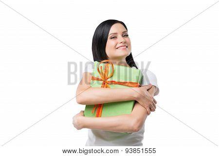 Happy Brunette Girl Hugs The Gift Box. Isolated.