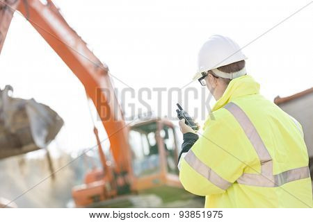 Supervisor using walkie-talkie at construction site against clear sky