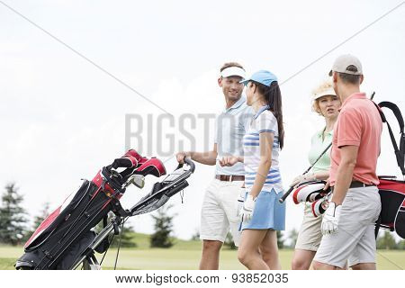 Friends communicating while walking at golf course against clear sky
