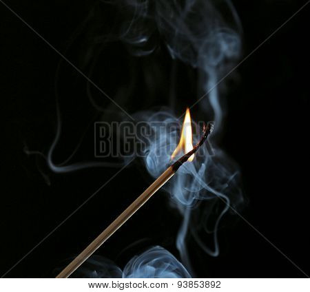 Burning match in smoke on dark background