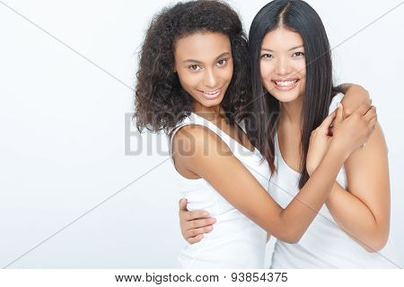Two positive girls embracing tightly