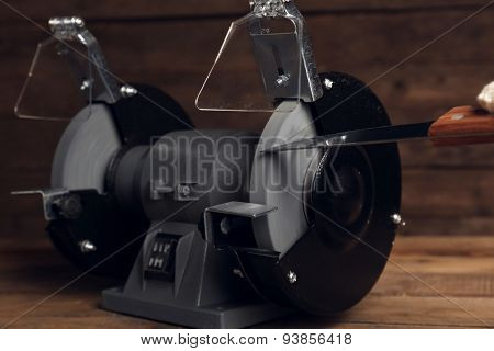 Knife sharpener and hand with knife on wooden table, closeup