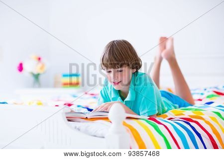 School Boy Reading A Book In Bed