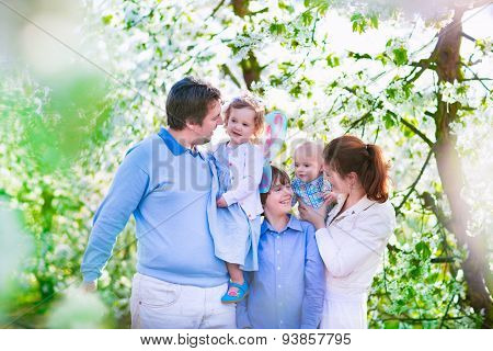 Happy Family In A Blooming Cherry Tree Garden