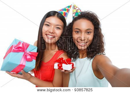 Cheerful girls holding birthday presents