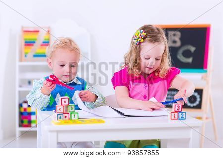 Kids at preschool. Two children drawing and painting at kindergarten.