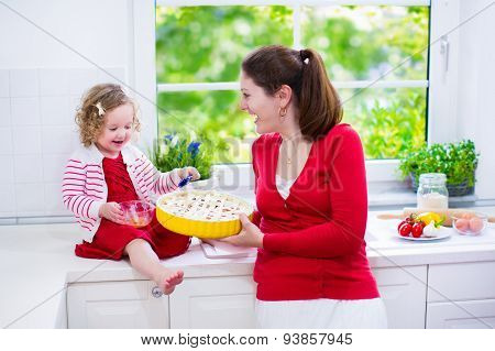 Young Mother And Daughter Baking A Pie Together