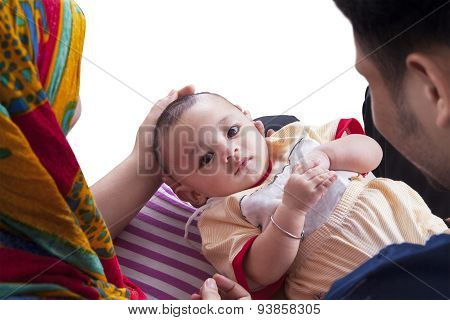 Cute Baby With Parents Look At The Camera