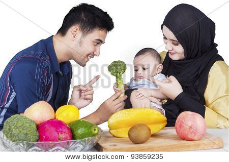 Father Showing Broccoli On His Baby
