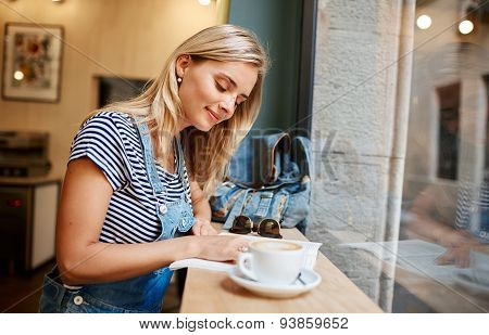 Beautiful Young Pregnant Girl Sitting In Cafe Reading Magazine And Drinking Coffee With A Croissant