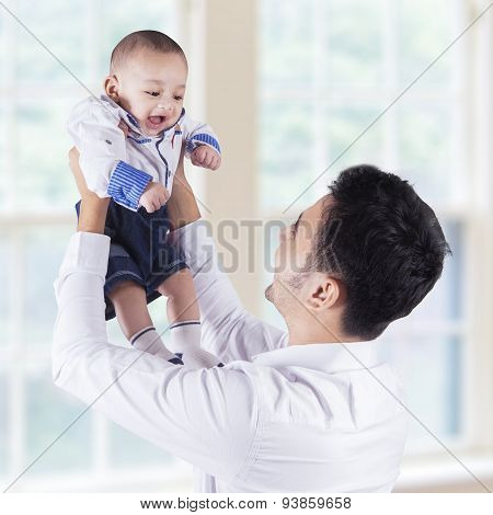 Happy Father Lift Up His Baby Near The Window