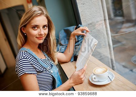 Portrait Of A Young Pregnant Girl Who Is Sitting In A Cafe Reading A Magazine And Drinking Coffee Wi