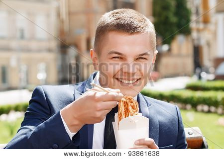 Happy businessman eating Chinese noodles