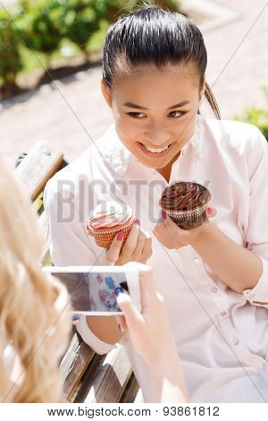 Girl taking picture of her friend with cupcakes