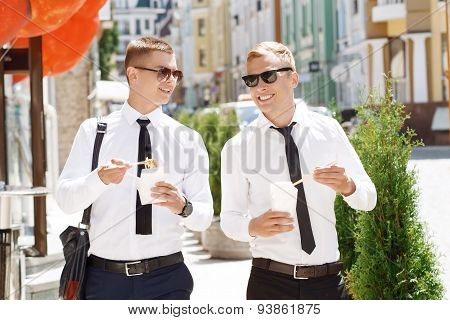 Pair of young men walking with street food