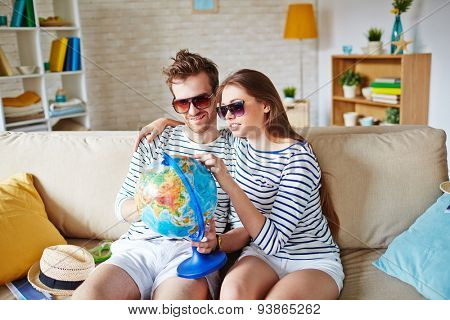 Amorous couple in sunglasses choosing place for travel and rest