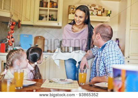 Family of four gathered in the kitchen for dinner