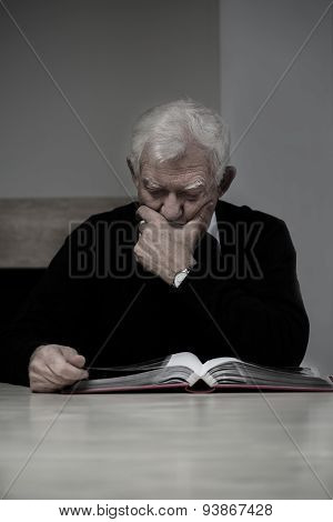 Old Man Looking At Photo Album